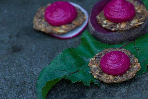 dark fuchsia colour hummus on seed crackers sitting on fresh beet slices, radish slices, beet leaf