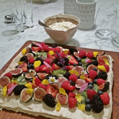 square pavlova dessert with lots of berries and edible flowers