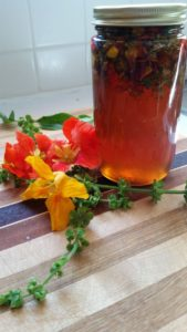 jar of honey infused with summer flowers and herbs