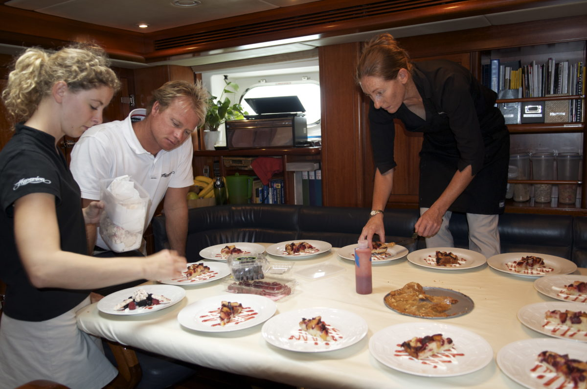Chef plating dessert for many on sailing yacht
