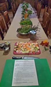 table lines with jars and bowls of fresh herbs, ribbon vegetables, cooking class