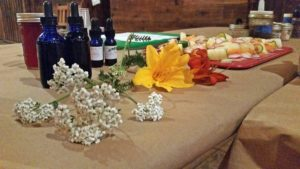 Food is medicine, flowers, tincture bottles, shaved vegetables, chopping board