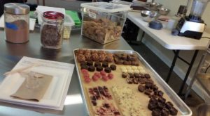 Tray of sample chocolate, containers of cacao ingredients workshop set up