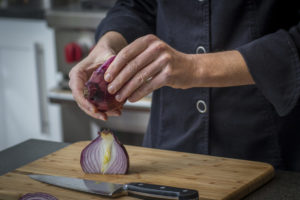 peeling a half chopped onion, knife skills