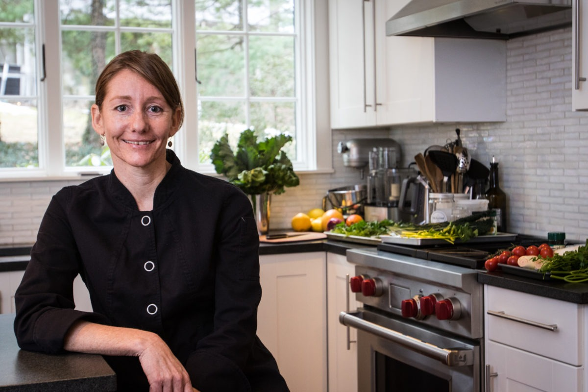 Profile picture of chef karina hines sitting in a kitchen, next to a stove with vegetables in the background