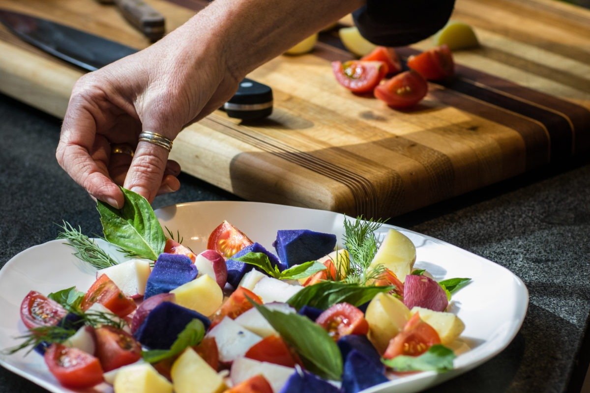 Chef hand garnishing a colourful potato, tomato and herb summer salad on a plate, knife and chopping board in the background