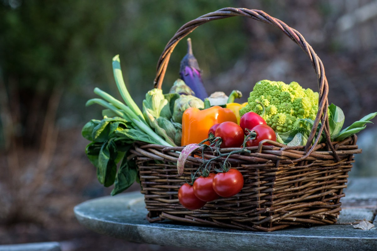 woven basket artfully filled with different colourful vegetables and fruits