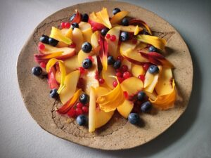 sliced fruit + blueberries + red currants + daylily petals on a platter